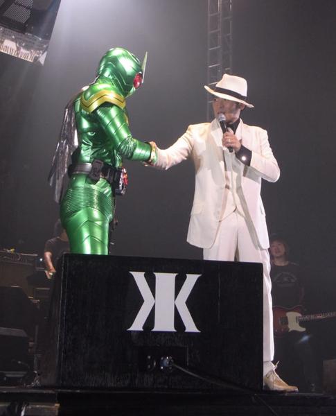 ライブで仮面ライダーと握手をする吉川晃司