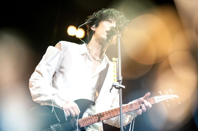 破れた白いシャツで歌っているRADWIMPSの野田洋次郎